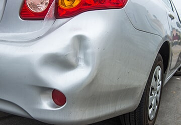 Silver Car with a Dent in Back — Auto Repair in Westbury, NY
